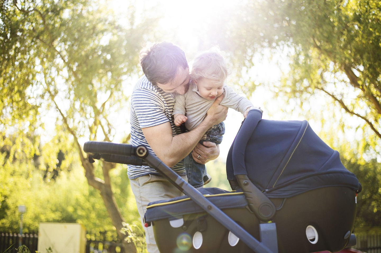 Vater mit Kinderwagen in der Natur