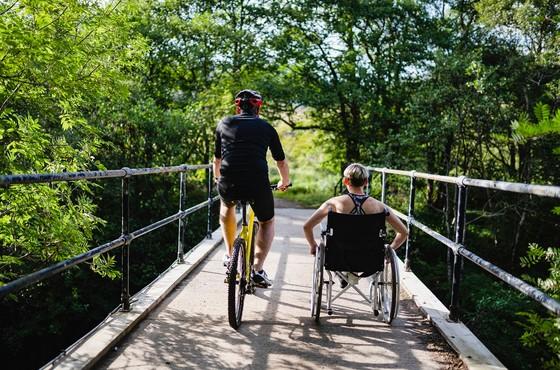 Mountainbiker und Rollstuhlfahrerin nebeneinander auf Holzbrücke