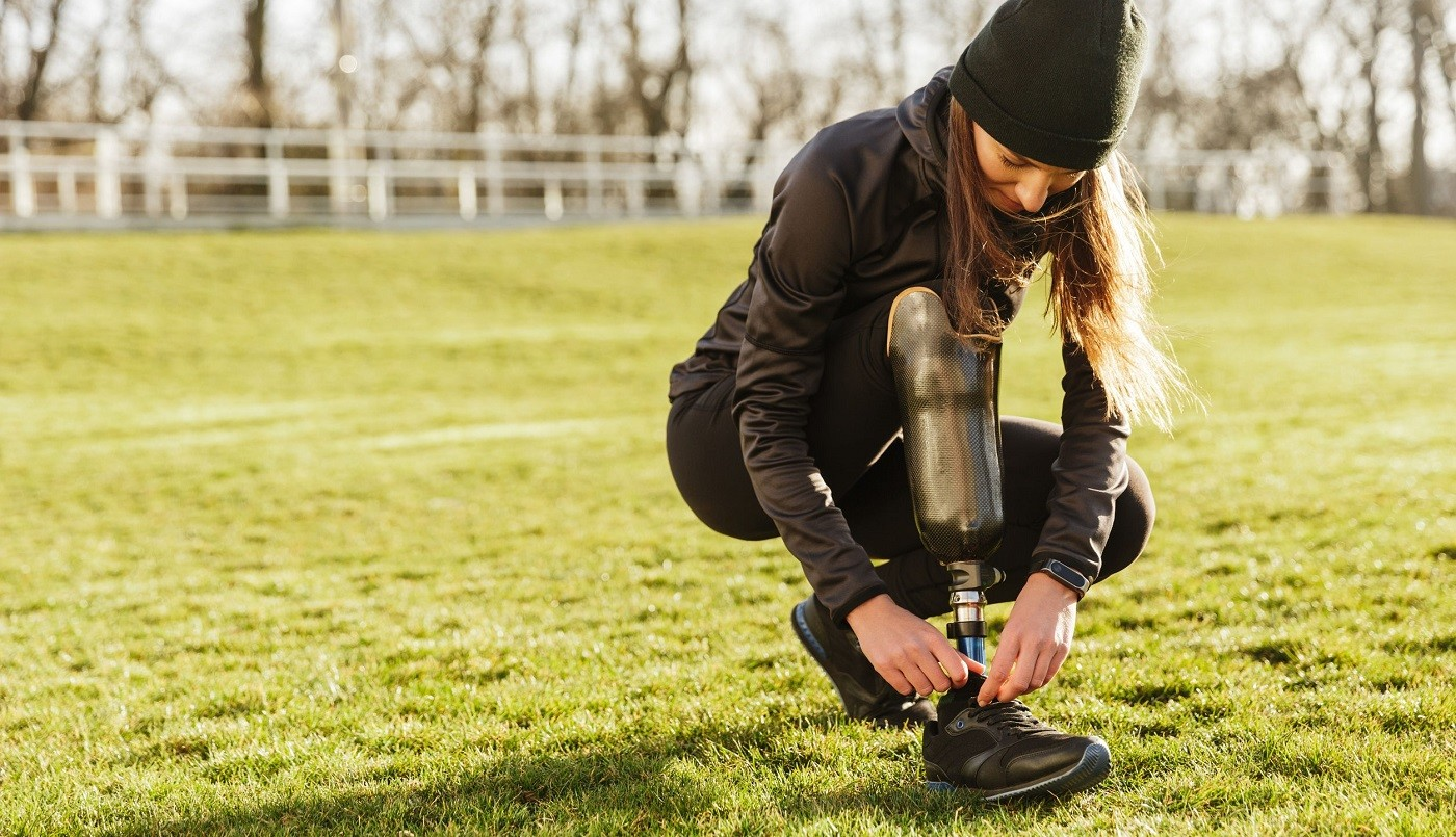 Frau mit Bein-Prothese bindet sich beim Sport machen den Schuh