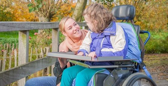 Kind im Rollstuhl mit Frau