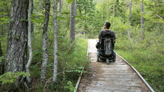 Mann in elektrischem Rollstuhl im Wald