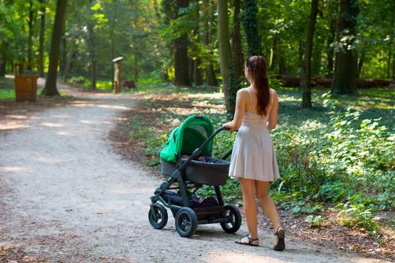 Frau mit Kinderwagen auf Waldweg