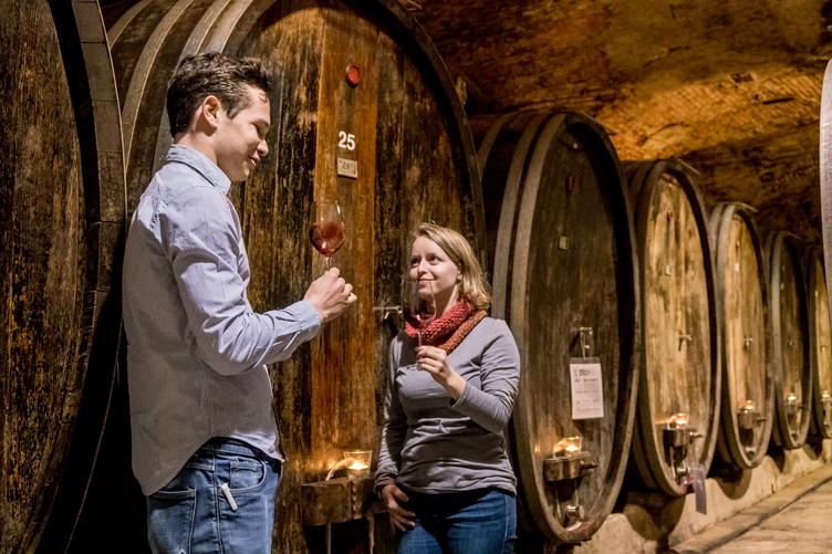 Frau und Mann probieren Wein vor großen Weinfässern